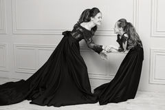 拥抱和看照相机的母亲和女儿 系列愉快爱 母亲和女儿美好的长的豪华蓝色dres的 免版税图库摄影