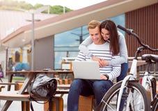 拥抱和看膝上型计算机的夫妇 免版税库存照片
