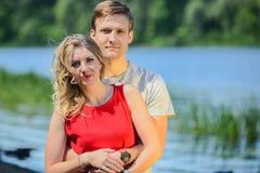 拥抱和笑在河背景的年轻愉快的夫妇 库存图片