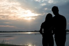 拥抱和观看日落的一个浪漫夫妇身分的剪影 拉丁文和爱概念 图库摄影