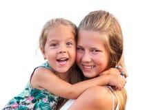 拥抱和调查照相机的两个姐妹乐趣 免版税库存图片