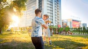 拥抱和转动他微笑的小小孩儿子的愉快的年轻父亲画象在公园 库存照片
