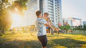 拥抱和转动他微笑的小小孩儿子的愉快的年轻父亲画象在公园 免版税图库摄影
