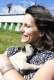 拥抱哈巴狗小狗微笑的妇女 图库摄影