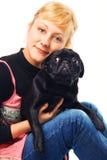 拥抱哈巴狗的逗人喜爱的金发碧眼的女人 免版税库存图片