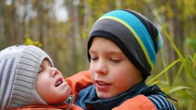 拥抱哭泣的弟弟和拿着他的男孩在我的胳膊 影视素材