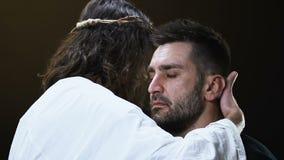 拥抱哭泣的男性教区居民的耶稣基督,做对罪孽的满意 股票视频