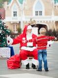 拥抱圣诞老人的男孩 库存图片