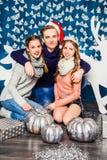 拥抱圣诞节d背景的男孩两个美丽的女孩  免版税库存图片