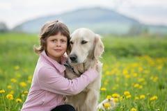 拥抱在一个室外设置的女孩一条大狗 免版税库存照片