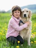 拥抱在一个室外设置的女孩一条大狗 库存图片