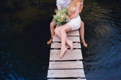 拥抱在一个木桥的一对肉欲的年轻夫妇的画象 免版税库存图片