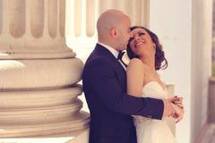 拥抱在专栏附近的新娘和新郎 免版税图库摄影