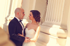 拥抱在专栏附近的新娘和新郎 免版税库存照片