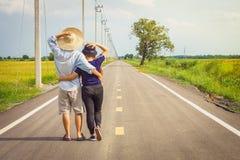 拥抱在乡下路的浪漫年轻亚洲夫妇 免版税库存照片