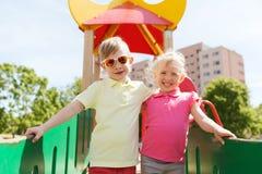 拥抱在儿童操场的两个愉快的孩子 库存图片