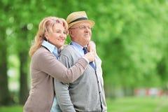拥抱在公园的无忧无虑的年长夫妇 库存照片