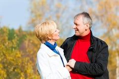 拥抱在公园的资深夫妇 免版税库存图片