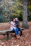 拥抱在公园长椅的夫妇在秋天 图库摄影