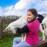 拥抱在农场的小女孩一只孩子山羊 免版税图库摄影