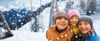 拥抱在冬天背景的愉快的孩子 免版税库存照片