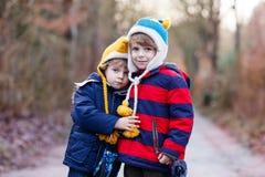 拥抱在冷的天的两个滑稽的小孩兄弟姐妹男孩 库存照片