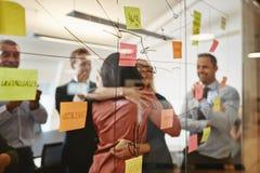 拥抱在办公室期间的两名女实业家群策群力会议 免版税库存照片