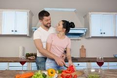 拥抱在厨房里的年轻美好的夫妇一起烹调沙拉 他们对彼此微笑 图库摄影