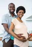 拥抱在厨房里的怀孕的夫妇 免版税库存图片