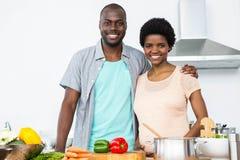 拥抱在厨房里的怀孕的夫妇 免版税库存照片