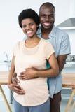拥抱在厨房里的怀孕的夫妇 库存照片