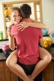 拥抱在厨房里的浪漫夫妇 库存照片