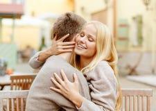 拥抱在咖啡馆的浪漫愉快的夫妇 免版税图库摄影