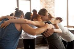 拥抱在圈子的青年人一起站立,小组团结 免版税库存照片