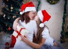 拥抱在圣诞树下的母亲和女儿 图库摄影