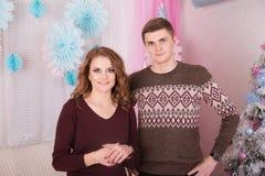 拥抱在圣诞树庆祝附近的年轻愉快的夫妇 图库摄影