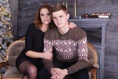 拥抱在圣诞树庆祝附近的年轻愉快的夫妇 免版税库存照片