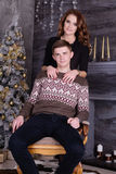 拥抱在圣诞树庆祝附近的年轻愉快的夫妇 免版税库存图片