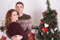 拥抱在圣诞树庆祝附近的年轻愉快的夫妇 免版税图库摄影