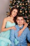 拥抱在圣诞树附近的家庭年轻有吸引力的夫妇的画象 库存图片