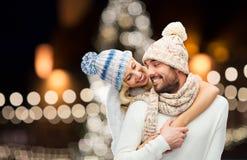 拥抱在圣诞灯的愉快的夫妇 免版税库存图片