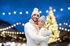 拥抱在圣诞灯的愉快的夫妇 图库摄影