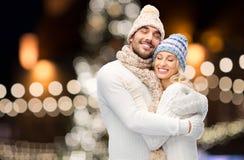拥抱在圣诞灯的愉快的夫妇 免版税库存照片