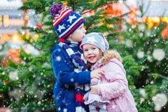拥抱在圣诞节市场上的两个小孩 免版税库存照片