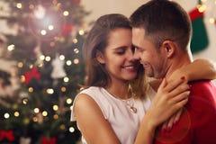 拥抱在圣诞节时间的年轻夫妇 库存照片