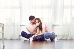 拥抱在地板上的一对爱恋的夫妇反对窗口 免版税库存图片