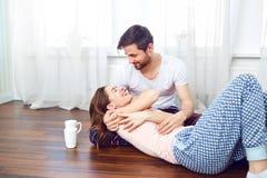 拥抱在地板上的一对爱恋的夫妇反对窗口 免版税库存照片