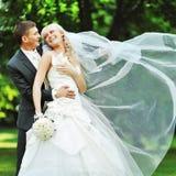 拥抱在夏天公园的婚礼夫妇 库存照片