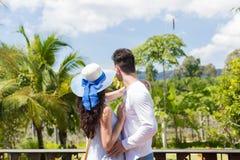拥抱在夏天大阳台或阳台愉快的妇女和人的年轻夫妇看热带森林 库存照片