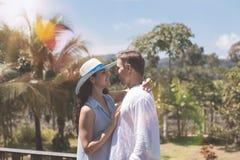 拥抱在夏天大阳台或阳台的年轻夫妇在美好的热带风景 库存照片